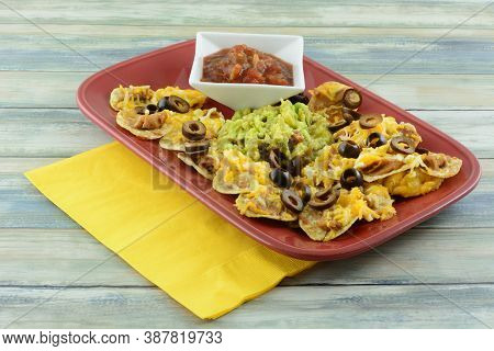 Nachos With Cheese, Bean Dip, And Clack Olives With Guacamole In Middle And With Salsa In Small Whit