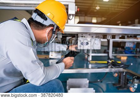 Asian Man Mechanic Technician Worker Working Install And Checking The Electric Control Cabinet Of Co