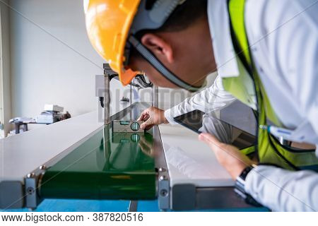 Asian Man Mechanic Technician Worker Use A Water Level Meter Working And Assemble The Product Sortin
