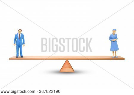 Gender Equality Concept : Male And Female Miniature Figure People Balancing On Seesaw Or Balance Sca