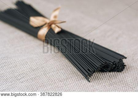 Raw Black Homemade Spaghetti Bunch On Canvas Rag. Dry Black Noodles Macaroni Bundle.