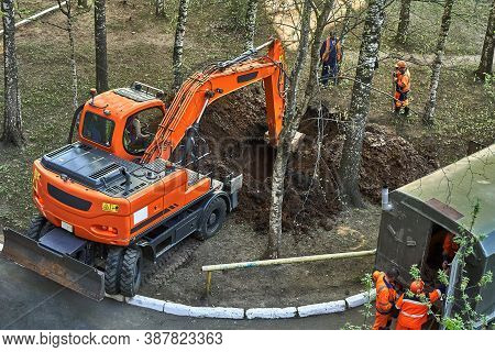 Mini Excavator Digging A Trench Among The Trees For Repairing City Communications