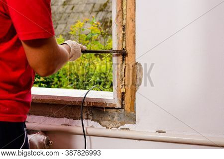 The Man With A Hand Saw Cuts The Mounting Wool Around The Window Frame, Installation Of An Old Woode