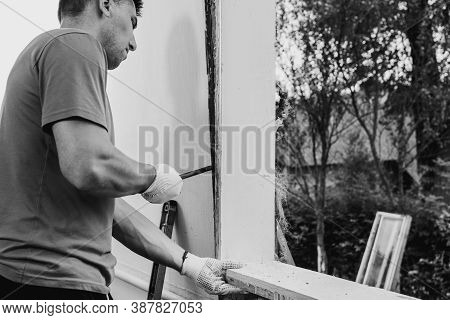 The Master Dismantles The Old Window With A Crowbar, Weighs The Old Window Frame From The Wall With