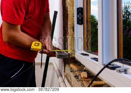 The Man Performs Installation Work With The Window, For This He Also Uses A Tape Measure, Measures D