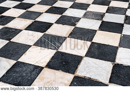 Black And White Checkerboard Tiles, Old With Scratches And Scuffs.