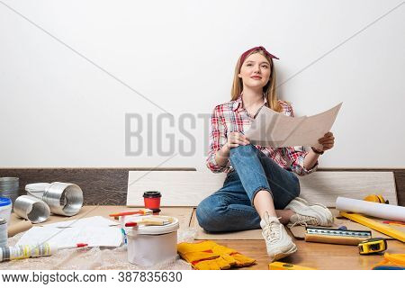 Smiling Girl Sitting On Floor And Holding Paper Blueprint. Home Remodeling And House Interior Redesi