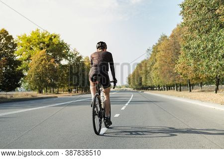 Man On A Gravel Bike On The Road, Back View. Well Equipped Cyclist Riding A Modern Bicycle Outdoors