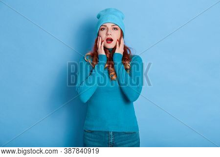 Ginger Girl Looks At Camera With Widely Opened Mouth, Touches Her Cheeks With Palms, Lady Wearing Ca