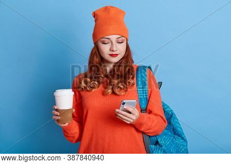 Photo Of Young Woman Feels Good From Received Email, Holds Coffee To Go, Has Backpack, Carries Rucks