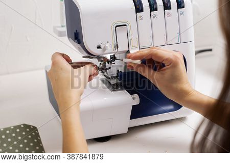 Women At Work: Girl Threading The Needle Of A Sewing Machine.
