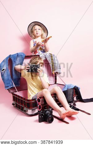 Travel: Children Little Boy And Girl Pack Things In A Big Red Suitcase For Travel. The Child Holds I