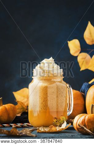 Pumpkin Spiced Latte Or Coffee In Glass Mug On Blue Table. Autumn Or Winter Hot Drink In Festive Nat