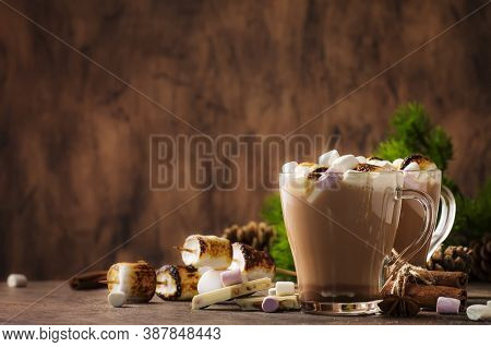 Hot Cocoa Or Chocolate With Marshmallow In Glass Mug And Winter Decoration On Wooden Table. Concept