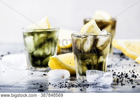 Healthy Food And Drink Concept: Iced Black Detox Lemonade Water With Crushed Ice And Lemon Slices In