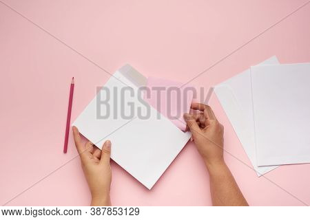 Two Female Hands Hold A White Paper Envelope Over A Pink Surface, Top View
