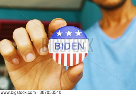 Bengkulu, Indonesia - October 03, 2020: Man Holding Biden Vote Button For The November Elections In