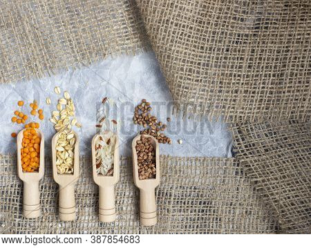 Wooden Scoops With Different Groats: Oatmeal, Lentil, Buckwheat And Rice Flat Lay