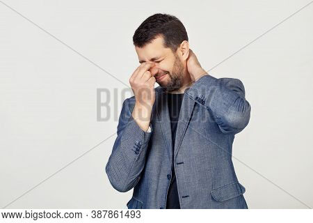 Young Businessman Man With A Beard In A Jacket, Tired Of Rubbing His Nose And Neck, Feeling Tired An