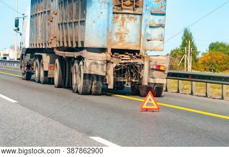 Old Truck Stands Broken On The Highway Putting Up An Emergency Stop Sign On A Clear Summer Day