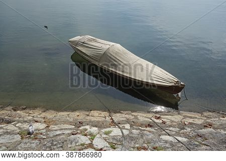 Boat Anchored On Bank Of Maggiore Lake, Italy
