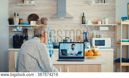 Senior Couple During Video Conference With Doctor Using Laptop In Kitchen Discussing About Health Pr