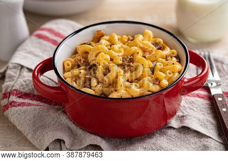 Bowl Of Macaroni And Cheese With Bacon Pieces On A Wooden Table