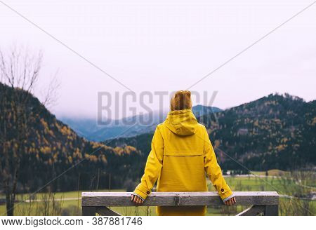 Woman In Yellow Jacket On Nature Background Of Mountains.