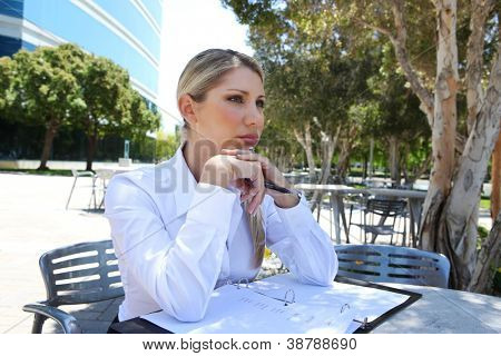 A pretty blonde business woman at office in deep concentration