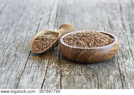 Heap Of Flax Seeds Or Linseeds In Spoon Or Bowl On Rustic Background. Flaxseed Concept, Dietary Fibe