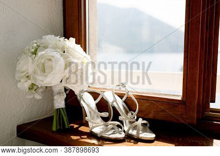 White Sandals Of The Bride On The Windowsill With A Bouquet Of Roses On A Wooden Windowsill By The W