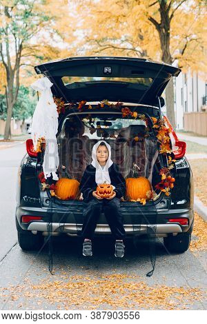 Trick Or Trunk. Child Boy Celebrating Halloween In Trunk Of Car. Kid With Red Carved Pumpkin Celebra
