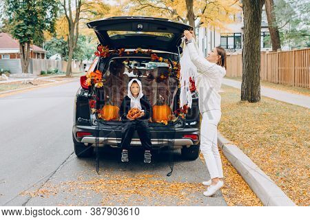 Trick Or Trunk. Child Boy With Red Pumpkin For Halloween Sitting In Trunk Of Car. Mother Decorating