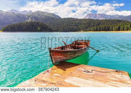 Lonely Boat In The Black Lake Of The Durmitor Area In Montenegro