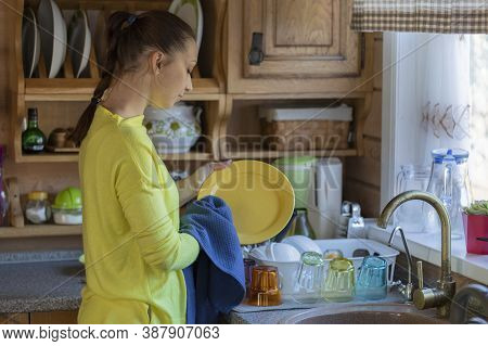 Beautiful Housewife Washing Dishes While Cleaning Kitchen, Young Woman Wipes Plate With Dry Waffle T
