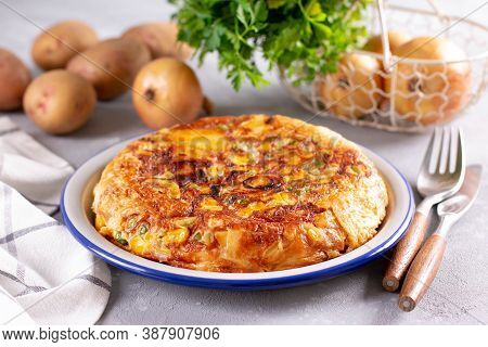 Frittata Of Eggs, Potatoes, Paprika, Parsley, Green Peas, Onions, Cheese On A Plate On Light Backgro