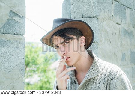 Fashion Young Man. Handsome Guy With Confident Face. Close Up Young Man Smoking A Cigarette. Man Wit