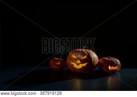 Halloween Card. Jack O Lantern With Candles Glow On A Black Background. A Row Of Creepy Pumpkins Wit