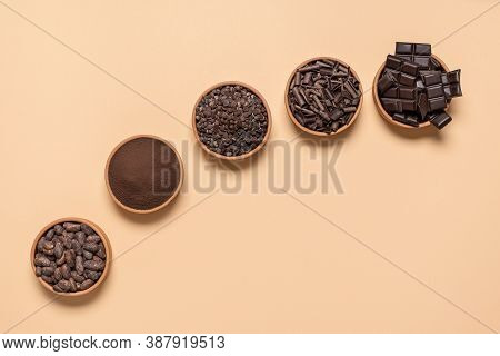 Organic Cacao Beans And Chocolate Chunks In Ceramic Bowls, Isolated On A Beige Background. Flat Lay