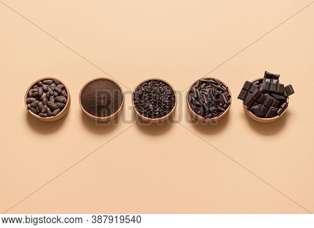 Chocolate Ingredients, Cacao Beans, Cocoa Powder, Chocolate Chunks In Bowls, Isolated On A Beige Bac