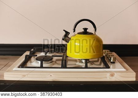 Yellow Steel Kettle On The Gas Hob On The Wooden Table. Modern Yellow Kettle On The Stainless Steel