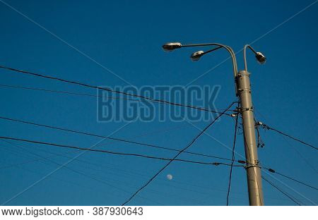 Ordinary City Lamppost With Three Glass Lamps. Black Wires All Around. Evening Blue Sky Background W