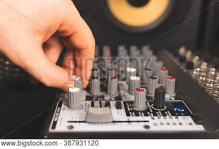 Sound Engineer Using Control Channels Of Studio Mixer.