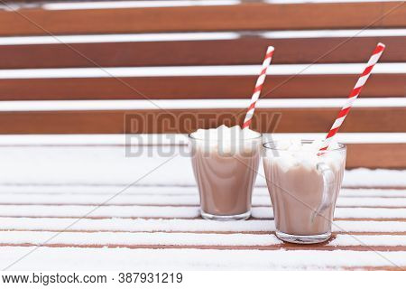 Glass Mugs, Cups With Hot Chocolate, Cocoa, Marshmallows. Winter Snow Covered Park Bench. Striped Re
