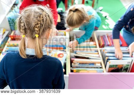 Little Girl Chooses, Takes Book With Fairy Tales From Box In Children's Library.special Reading Kids