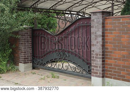 One Metal Gate With A Black Iron Pattern And Part Of A Wall Of A Fence Made Of Brown Bricks On The S