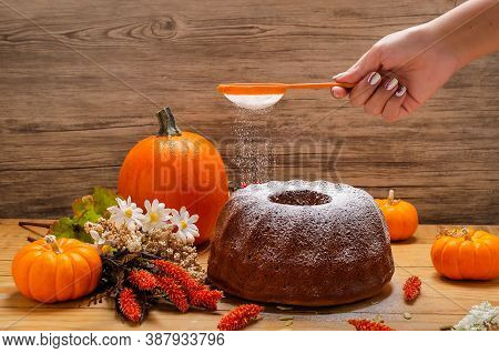 Pumpkin Muffin, On Wooden Table With Autumn Decoration. Person Putting Sugar To The Muffin.