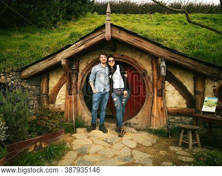 Couple Smiling In Front Of Porch Of Hobbit Hole At Hobbiton Movie Set. September 2020, Matamata - Ne