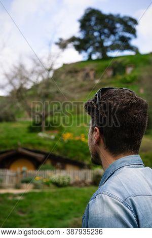 Man Looking At The Shire In Hobbiton Movie Set Tour. September 2020, Matamata, New Zealand.