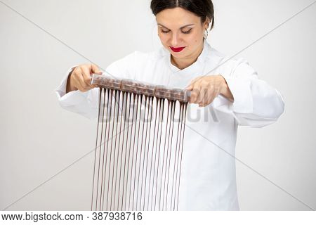 Attractive Female Chocolatier Pouring Excess Melted Dark Chocolate From Molds Preparing Chocolate Mo